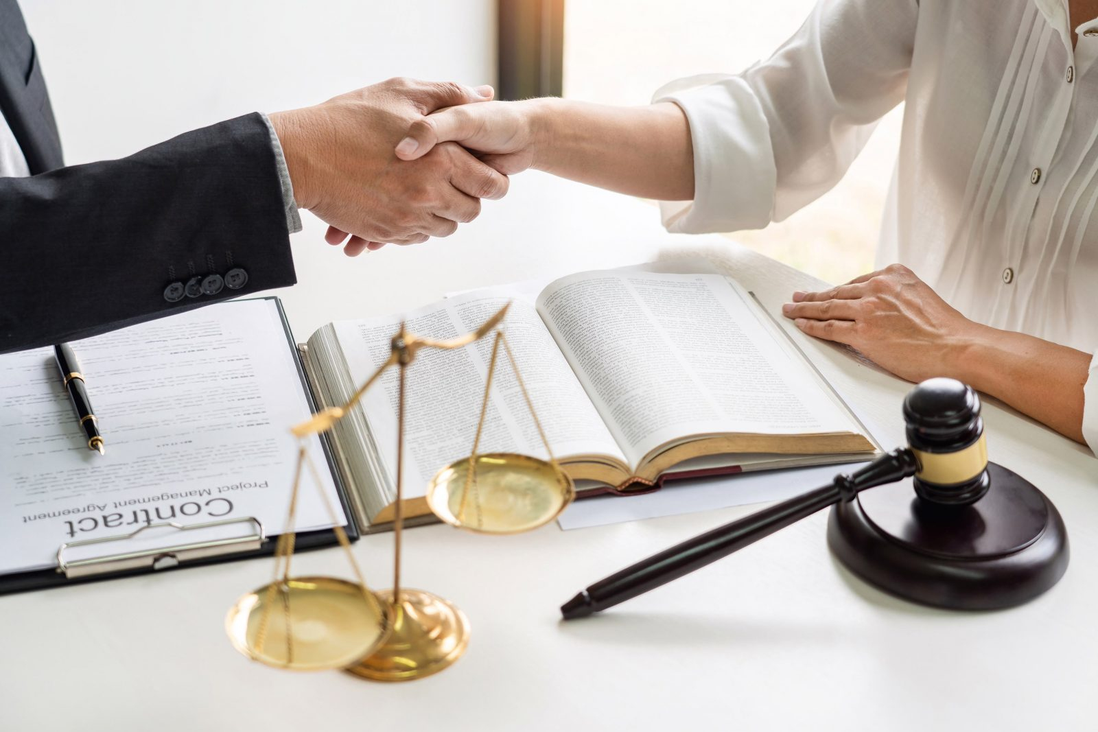 people shaking hands over a desk with a book, scales and other legal paraphernalia